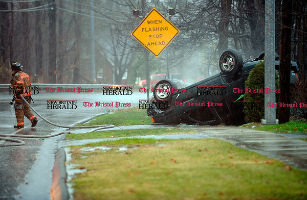 12/1/2010 Mike Orazzi | Staff A Bristol firefighter walks away from a Jeep Grand Cherokee after a one vehicle crash on Route 69 just North of Bristol Central High School on Wednesday afternoon shortly after 3 pm.