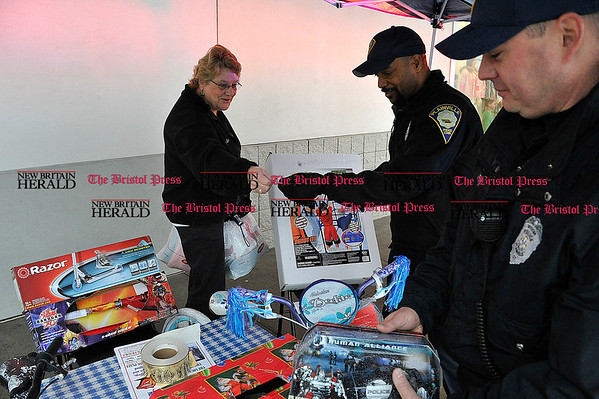 Rob Heyl Marilyn McGratti from Newington hands over a cash donation to Officer Miller as Officer Jamie Fenn places a donated toy away from the rain. 12.12.10 for 12.13.10