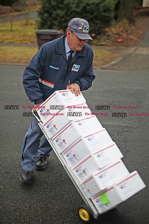 Chris Richie | Staff Letter carrier Henry Rodrigue loads packages destined to Marine's in Afghanistan, collected by Marjorie Hackett-Wallace in New Britain. Hackett-Wallace started sending care packages with the Marine Corps Family Foundation in 2008 when her son was stationed in Iraq. (12/13/10)