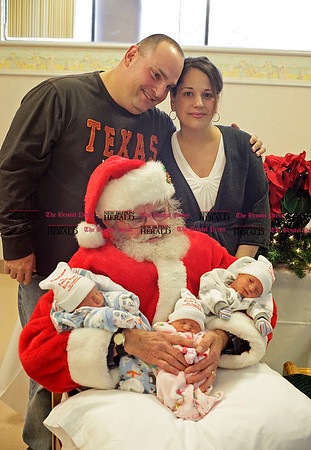Chris Richie | Staff Newborn triplets, left to right, boy Cooper, girl Jordan and boy Ty Gagliardi, pose with Santa at the Hospital of Central Connecticut on Tuesday. The three, who were born last Friday, are the children of Louis &quote;Rocky&quote; and Christine Gagliardi of New Britain. &quote;This is our Christmas miracle,&quote; said Louis, who is a physical education teacher at Smalley Academy in New Britain. Christine's birthday falls on December 21st, and as Louis says, &quote;It's going to be one big celebration in December in our household.&quote; Ty, Cooper and Jordan came in respectively at, 5lb. 4oz., 4lb. 14oz. and 4lb. 5oz. (12/14/10)