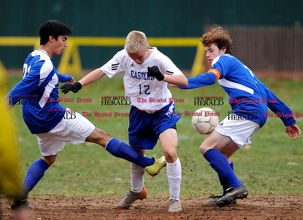 11/9/2010 Mike Orazzi | Staff Bristol Eastern's Nicholas Chaisson (12) between Fairfield Ludlowe's Christian Barral-Arteta (21) and Maximillian Grascher (7) at Muzzy Field on Tuesday afternoon during a Class L First Round Boys Soccer State Tournament game.