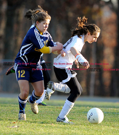 11/3/2010 Mike Orazzi | Staff Gilbert's Rachel Wendel (12) gives a little push to Terryville's Jessica Bednaz (18) during Wednesday's soccer match at the Fisher Middle School.