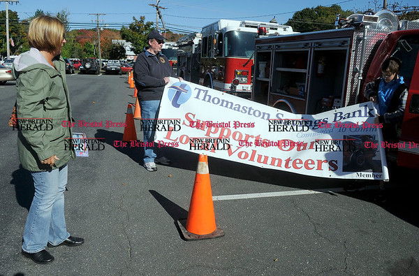 10/9/2010 Mike Orazzi | Staff Lisa Gracie looks on as Tom O'Hare and her son Sean unroll a banner during Fire Prevention Day in Adams Hometown Market parking lot off Route 6 on Saturday morning.