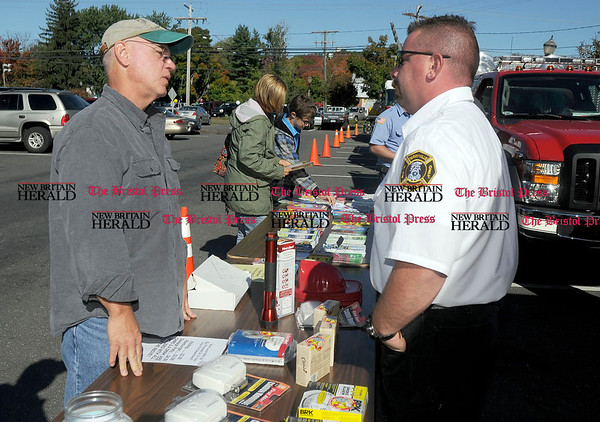 10/9/2010 Mike Orazzi | Staff Dave Boiland talks with Terryville fire captain Paul Grandbois during Fire Prevention Day in Adams Hometown Market parking lot off Route 6 on Saturday morning.