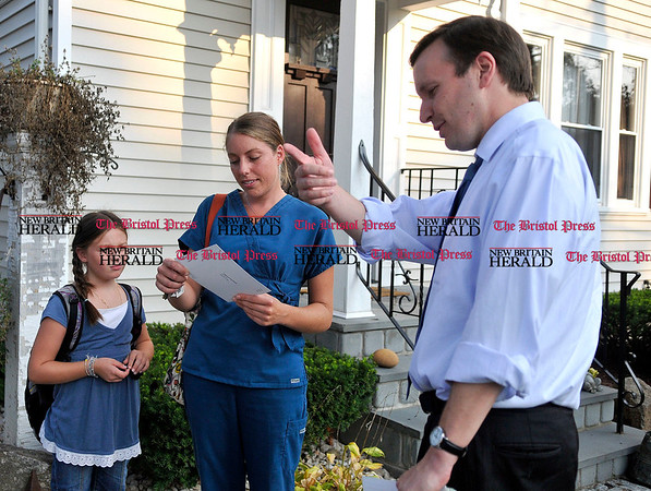 9/1/2010 Mike Orazzi | Staff STAND ALONE U.S. Congressman Chris Murphy (right) talks with Amie Zarrella and her daughter Madison Franco,8, while going door to door on Trumbull Avenue in Plainville on Wednesday evening.