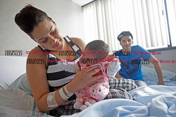 Chris Richie | Staff Giovanna Roman and Luis Torres with their daughter Giulianni Alessandra Torres at the The Hospital of Central Connecticut in New Britain. The family all share a birthday on February 10th. (2/11/11)
