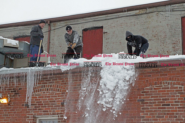 Samantha Burr Brad Weiland (left), Bob DiCarlo and Seth Weiland (right) shovel the roof of Gisele's Coiffures in Plainville. (2/1/11)