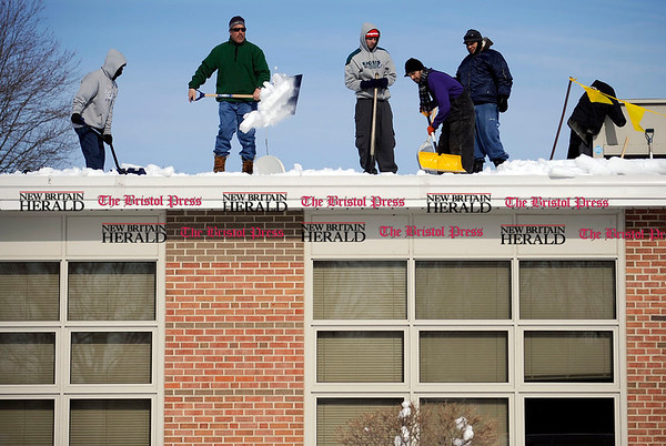 2/11/2011 Mike Orazzi | Staff Workers clear snow from the roof of Bristol Eastern High School on Friday morning.