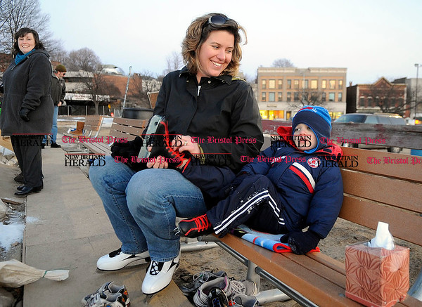1/6/2011 Mike Orazzi | Staff Lisa Lodge removes her son Stevie's skates after spending some time skating at the downtown rink in Depot Square on Thursday evening in Bristol.