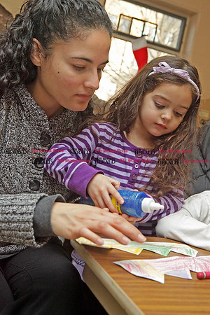 Chris Richie | Staff Leah Cordero and her daughter Elora, 3, decorate a paper crown to wear during the Three Kings Day celebration at the New Britain Youth Museum. (1/6/11)