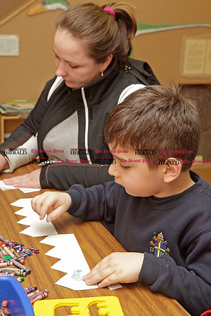 Chris Richie | Staff Anna Krzynowek and her son Adam Karacayli, 6, decorate paper crowns to wear during the Three Kings Day celebration at the New Britain Youth Museum. (1/6/11)