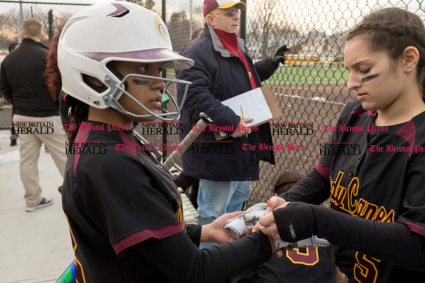 040317 Wesley Bunnell | Staff New Britain softball vs Bristol Central at Chesley Park in New Britain on Monday April 3, 2017. The game was scheduled to be played at Bristol but changed to New Britain due to field conditions with Bristol playing as the home team. Nariely Andujar (12) , left, receives help with her batting gloves from Amanda Jacobs (5).