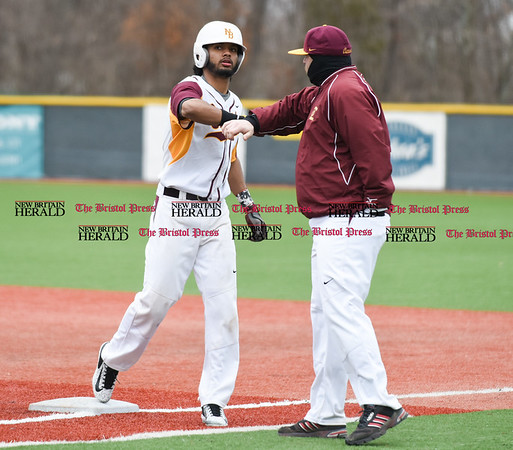 040717 Wesley Bunnell | Staff New Britain High School baseball defeated E.C. Goodwin Tech in a game played at CCSU on Friday afternoon. Josh Garcia (7) is congratulated by the first base coach after running out an infield single.