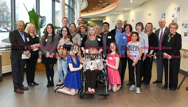 040717 Wesley Bunnell | Staff An Art of Honor Exhibition was held at The Hospital for Special Care on Friday evening. The exhibition featured art work by veterans and their families. Artists along with their families and guests gather for a photo.
