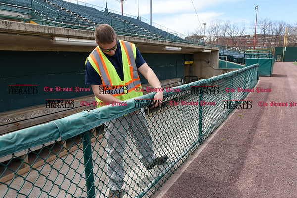 041017 Wesley Bunnell | Staff Stadium preparation continues at the home of the New Britain Bees on Monday April 10. Josh Prior uses plastic ties to secure the padding on the visitors side dugout rail.