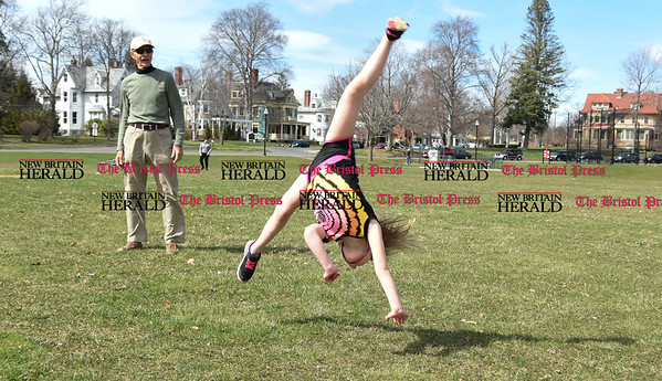 041017 Wesley Bunnell | Staff Central Park was packed with visitors enjoying a warm spring day on Monday April 10. Bella Vinci, age 7, performs a cartwheel with no hands as her grandfather Frank Vinci watches.