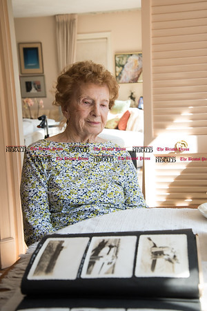 030617 Wesley Bunnell | Staff Farmington resident Ola Ferla served as an Army Nurse during WWII in Scotland and England. Ola looks through photographs taken by her late husband Joseph who was also a WWII veteran.