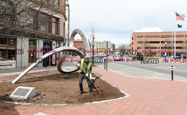 041717 Wesley Bunnell | Staff A city worker plants flowers and puts down fresh mulch around the sculpture Home by artist Craig M. Frederick at the corner of Main & Arch St on Monday April 17.