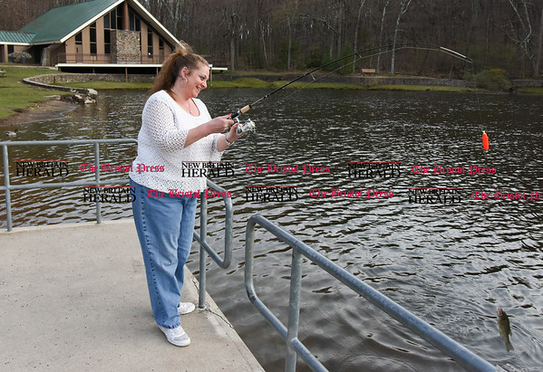 041717 Wesley Bunnell | Staff Deidre Methe reels in a large mouth bass at Page Pond on Monday April 17 which was released.