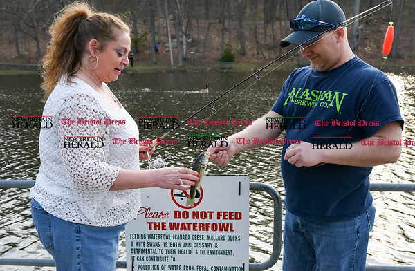 041717 Wesley Bunnell | Staff Deidre Methe gets help from Roman Kochanski in removing a large mouth bass from her hook and releasing it back into Page Pond on Monday April 17.