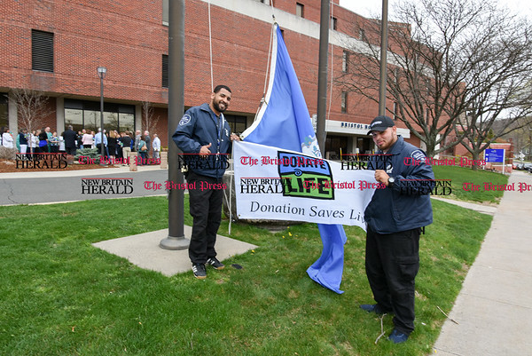 041917 Wesley Bunnell | Staff Life Choice and New England Donor Services held a flag raising ceremony at Bristol Hospital on Wednesday afternoonin honor of April as National Donate Life Month to encourage people to sign up as organ donors. Bristol Hospital security readies to raise the flag as the crowd in the background gathers for a small ceremony.