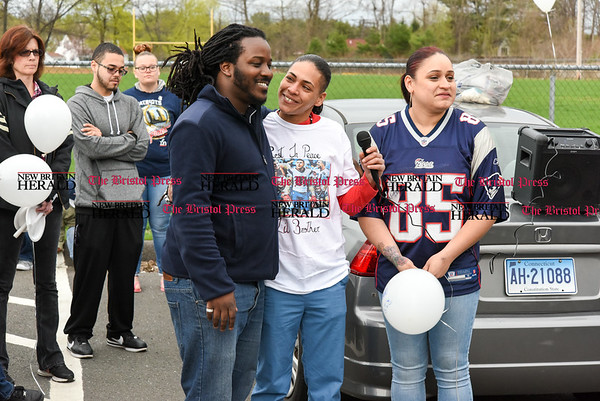 042417 Wesley Bunnell | Staff A candlelight vigil was held at Casey Field in Bristol by family and friends of former New England Patriot Aaron Hernandez. Sarah Hernandez, middle, and Maria Santiago stand with a family friend enjoying a lighter moment at the vigil.