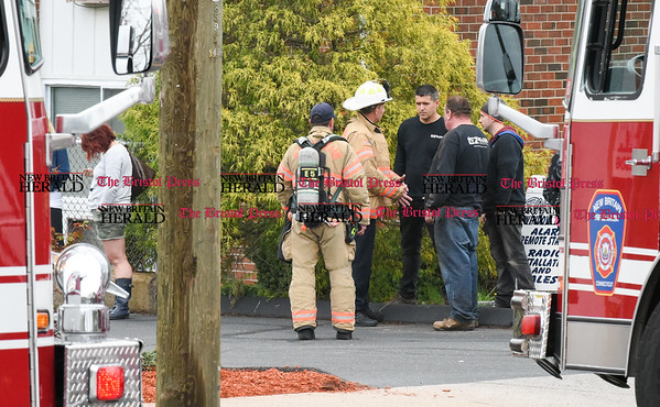 042717 Wesley Bunnell | Staff Deputy Fire Chief Tom Leahey of the New Britain Fire Department speaks with workers from EZ Welding of New Britain after a small acetylene tank EZ Welding was using caught fire shutting down a section of South Main St near Columbia Dental on Wednesday afternoon.