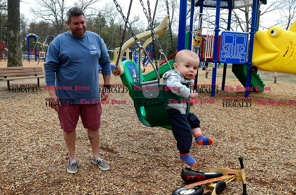 4/27/2017 Mike Orazzi | Staff Michael Nolan and his son Conor, 9 months, while enjoying the recently renovated playground in Plainville's Norton Park Thursday.