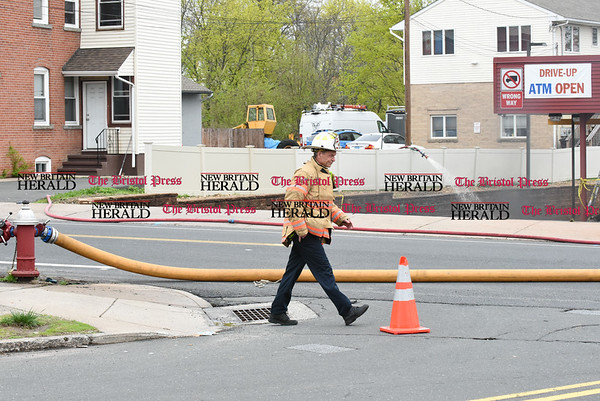 042717 Wesley Bunnell | Staff Deputy Fire Chief Tom Leahey of the New Britain Fire Department walks down South Main St as a unmanned fire hose pours water onto a small acetylene tank which caught fire on Wednesday afternoon. The fire occurred in the driveway adjacent to Columbia Dental on South Main while being operated by EZ Welding of New Britain.