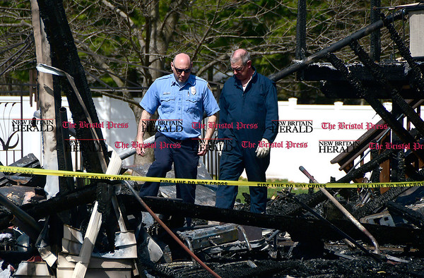 4/11/2017 Mike Orazzi | Staff Southington fire inspectors Len Chozick and Bob Hunt survey the damage at a fire scene on Fleetwood Road in Southington.