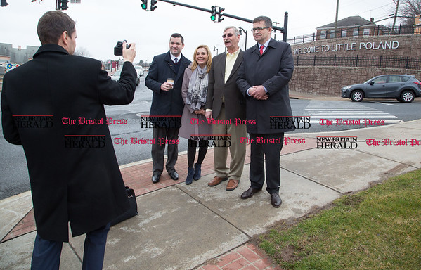 From left, Darek Barchikowski, Honorary Consul for Poland, takes a picture of Adrian Baron, Sabina Klimek, Lucian Pawlek, and Ambassador Piotr Wilczek standing in front of the Welcome to Little Poland sign on the corner of Main Street and North Street in New Britain. The Polish ambassador to the United states visited several businesses along Main and Broad Streets and visited the new Honorary Consulate of the Republic of Poland on Broad Street, April 1, 2017. (Photo by Christopher Zajac