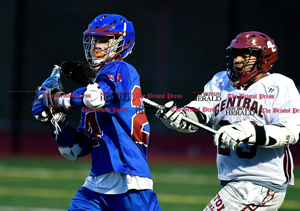 4/1/2017 Mike Orazzi | Staff St. Paul Catholic High School's Tucker Raymond (24) and Bristol Central's Joshua Carrasquillo (29) during lacrosse Saturday night at BC.