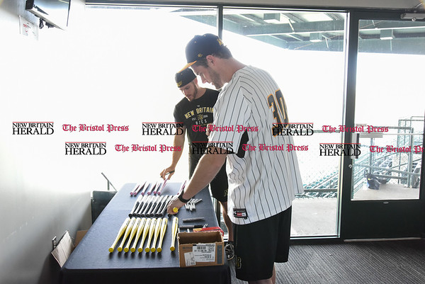 041117 Wesley Bunnell | Staff The New Britain Bees held their media day on Tuesday afternoon before holding open tryouts later in the evening. Brian Dupra (30) and Eric Fornataro add their signatures to Bees team signed mini bats.