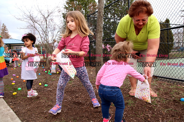 Kayleigh Spada, Alice Reilly and Sadie Montiniere collect eggs with the help of licensed childcare provider Laurie Wojnarowski at Stocks Playground.