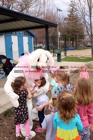 Mia Finnegan hugs the Easter Bunny at the holiday gathering of licensed childcare providers and the children in their care at Stocks Playground.