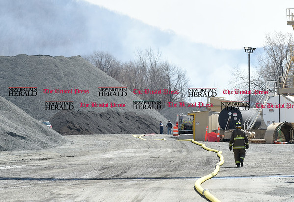 041317 Wesley Bunnell | Staff A Newington Firefighter walks towards the scene of a fire at an unused building at Tilcon on Hartford Ave in Newington on Thursday afternoon.