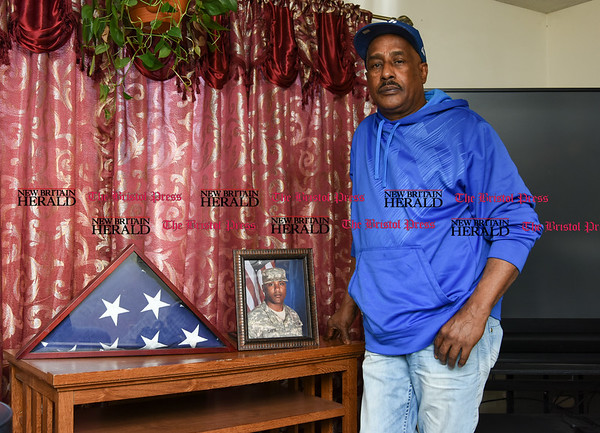041317 Wesley Bunnell | Staff Selwyn Cartie Sr. poses near a photo and folded American Flag from the funeral of his son Julian Cartie who was shot to death on Feb. 22, 2009. Julian's killer Michael Rodriguez was recently convicted and is set to be sentenced on April 19 in Springfield Mass. where the shooting occurred.