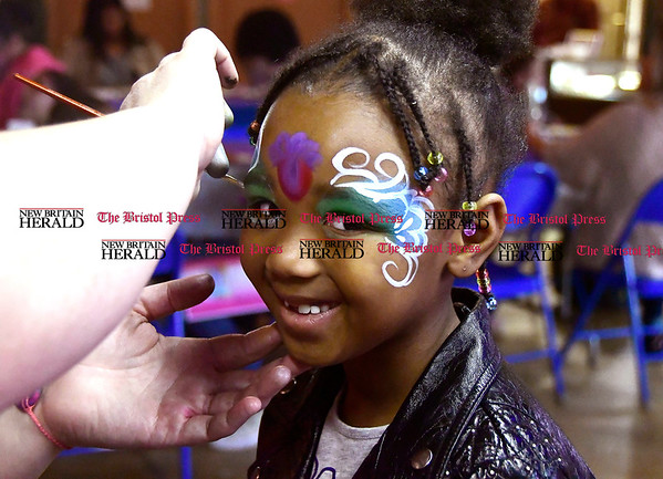 4/15/2017 Mike Orazzi | Staff Milan Onyejekwe has her face painted by Lonnie DiNello during the Annual Easter Egg Hunt at Trinity-on Main Saturday in New Britain.
