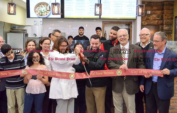 042517 Wesley Bunnell | Staff Mayor Erin Stewart along with restaurant owner Vincent Placeres, family and city officials held a ribbon cutting for Mofongo Restaurant which opened recently on West Main St across from city hall.