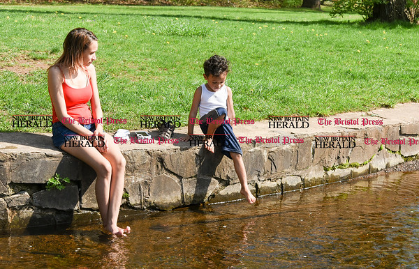 042817 Wesley Bunnell | Staff Zuleika Casiano sits along a stream at A.W. Stanley Park as she waits for son Justin Serrano, age 4, to stick his feet in to cool down on a warm Friday afternoon.