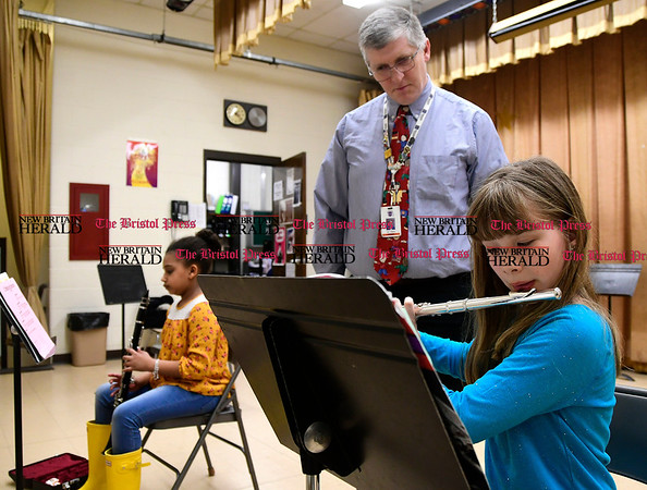 4/6/2017 Mike Orazzi | Staff Ken Bagley, citywide coordinator for music director, as South Side School 4th grade students Lily Hinton and Gwen Tanner (foreground) practice.