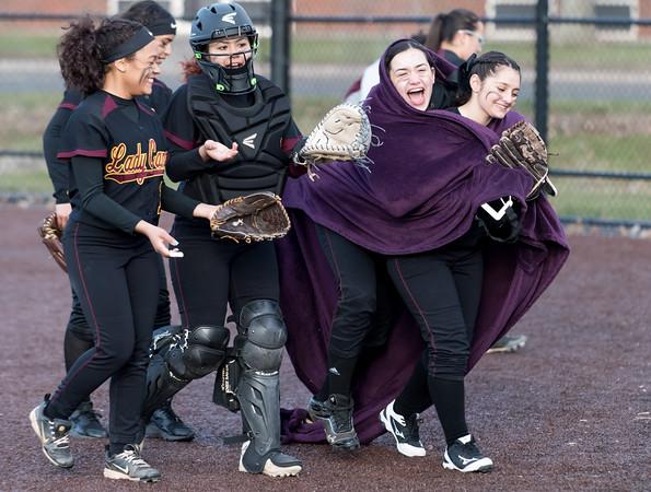 04/05/18 Wesley Bunnell | Staff New Britain softball defeated Newington on Thursday afternoon at Chesley Park for the schools first win over Newington in 11 games. Wearing a blanket on the field between innings Amanda Jacobs (5) celebrates with teammates.