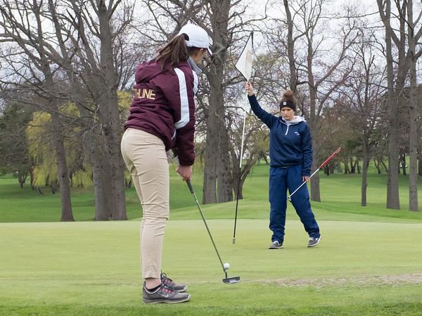 04/30/18 Wesley Bunnell | Staff Newington girls golf vs New Britain on Monday afternoon at Indian Hill Golf Club in Newington. New Britain's Cate Keithline putts on the first green while Newington's Jessica Pierschalski pulls the flag.