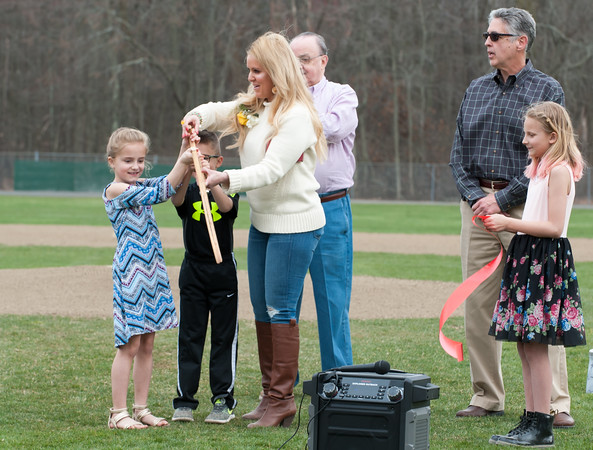 04/13/18 Wesley Bunnell | Staff Paul Baretta's daughter, Andrea Baretta-Maule cuts the ceremonial ribbon with the help of her two children Nerea and Trey during the an official dedication ceremony. The Town of Berlin dedicated Paul Baretta Field at Percival Park on April 13th before the Berlin High School baseball game vs Northwest Catholic.