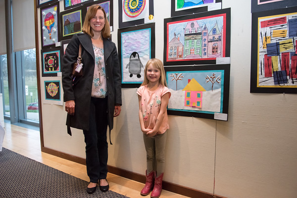 04/17/18 Wesley Bunnell | Staff Ava Matteson, age 6, stands next to her mother as she smiles and shows her artwork of a house she created as a student of Griswold Elementary School. An opening reception was held Tuesday night at the New Britain Museum of American Art featuring creative artwork from Berlin Public School students.