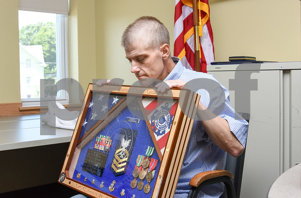 080917 Wesley Bunnell | Staff A retirement ceremony was held for Coast Guard Chief Scott Johnson at the New Britain Fire Department Headquarters on Wednesday at noon. Johnson who is battling colorectal cancer has worked as a firefighter in New Britain for approximately 10 years. Johnson looks over the shadow box which was custom made by Coast Guard DC1 Wade Hinkley.