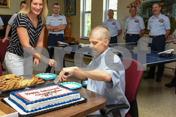 080917 Wesley Bunnell | Staff A retirement ceremony was held for Coast Guard Chief Scott Johnson at the New Britain Fire Department Headquarters on Wednesday at noon. Johnson who is battling colorectal cancer has worked as a firefighter in New Britain for approximately 10 years. Johnson slices his retirement cake as firefighters and Coast Guard members look on.
