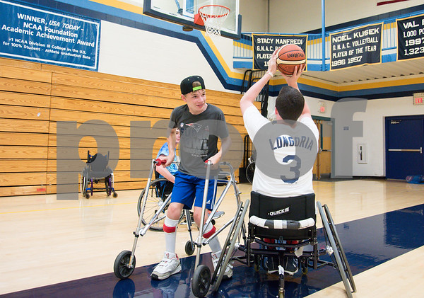 080217 Wesley Bunnell | Staff Camper Joe Grindrod , middle, guards volunteer Kyle McCormick during a game of basketball at the Hospital for Special Care Ivan Lendl Adaptive Sports Camp on Wednesday afternoon at the University of St. Joseph in West Hartford.