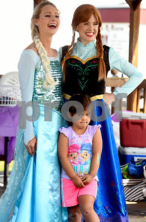 8/26/2017 Mike Orazzi | Staff Jordan Witik as Elsa and Sarah Keck as Anna pose with Lylah Arriola,4, during the Terryville Lions County Fair Saturday morning.