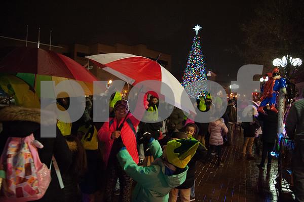 12/05/17 Wesley Bunnell | Staff New Britain held their annual Tree Lighting at Central Park on Tuesday evening with a visit from Santa Claus. A passing shower forced umbrellas to come out in the crowd as they await their turn with Santa.